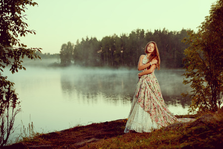Luxury woman in a forest in a long vintage dress near the lake. Girl meets sunrise in summer forest photo