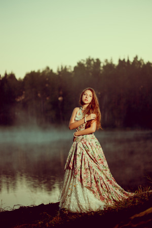 wood nymph: Luxury woman in a forest in a long vintage dress near the lake. Girl meets sunrise in summer forest