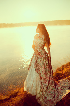 the long lake: Luxury woman in a forest in a long vintage dress near the lake. Girl meets sunrise in summer forest