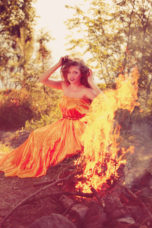 Beautiful witch in the woods near the fire. Magic woman celebrating Halloween. Girl doing witchcraft in the forest. photo
