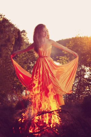 Beauty witch in the woods near the fire. Magic woman celebrating Halloween. Girl doing witchcraft in the forest. photo
