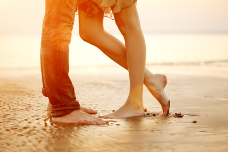 若い愛するカップル抱き締めると夕暮れ時のビーチでキスします。2 人の恋人、人および女性は水の近く裸足。愛の夏