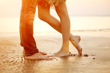 Een jonge liefdevolle paar knuffelen en zoenen op het strand bij zonsondergang. Twee geliefden, man en vrouw op blote voeten in de buurt van het water. Zomer in de liefde