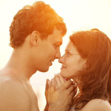 A loving young couple hugging and kissing on the beach at sunset. Two lovers, man and woman near the water. Summer in love