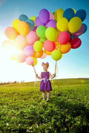 Happy little girl holding colorful balloons. Child playing on  green meadow. Smiling  kid. Portrait of baby outdoor  photo