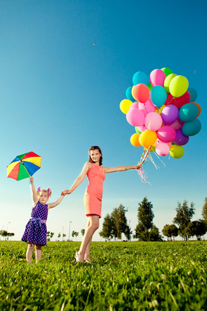 Beautiful little girl with mother colored balloons and rainbow umbrella holding  in  the park. Smiling child and mom on a field with flowers. Kid with mum rest on the  nature. Family outdoor photo