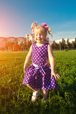 hair bow: Cute little girl  on the grass in the park. Smiling nice child on a field with  flowers. Kid rest on the nature. Portrait of baby outdoor Stock Photo