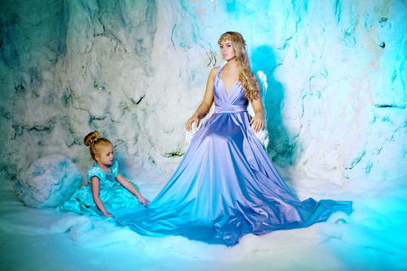Little girl with mother in princess dress on a background of a winter fairy tale. Baby and mom snow queen. Sweet smiling child and mum snowy kingdom. Kid in in carnival costume photo