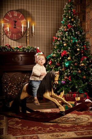 baby near christmas tree: Nice little baby near the Christmas tree. Little boy celebrating Christmas. Cute smiling child with New Year gifts. Christmas Toddler riding a toy horse