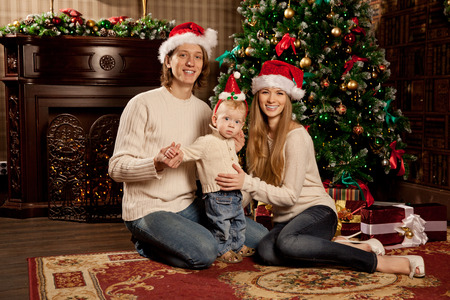 baby near christmas tree: Happy smiling young family near the Christmas tree celebrate New Year. Mom dad and kid at Christmas tree. Mother father and child on Christmas Eve. Mummy, Daddy and Baby.