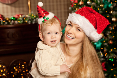 baby near christmas tree: Happy young smiling family near the Christmas tree celebrate New Year. Mom and kid at Christmas tree. Mother and child on Christmas Eve. Mummy and Baby.