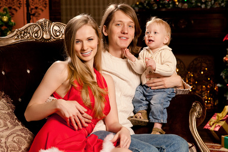 baby near christmas tree: Happy smiling family near the Christmas tree celebrate New Year. Mom dad and kid at Christmas tree. Mother father and child on Christmas Eve. Mummy, Daddy and Baby.