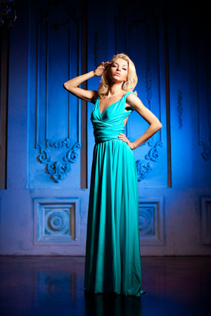 Beauty woman like a princess in the palace. Luxurious rich fashion stylish girl in a  long evening dress. photo