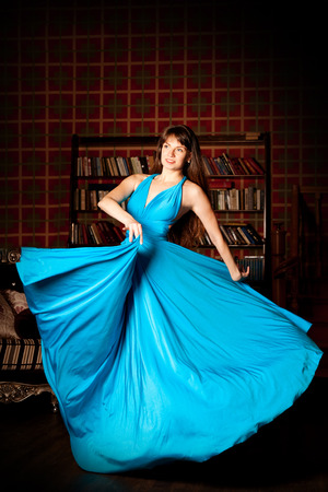Beauty woman in a long blue dress in the rich interior. Young girl in a long dress fashionable luxury in a library photo