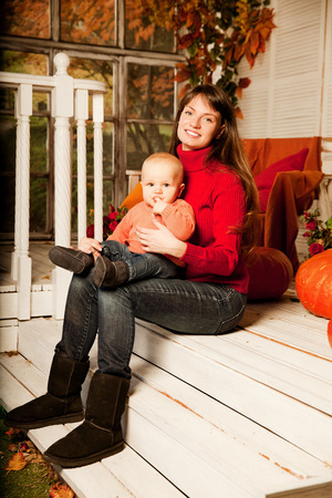 Beautiful woman with a child on the front porch with pumpkins autumn. Smiling mother and son. photo
