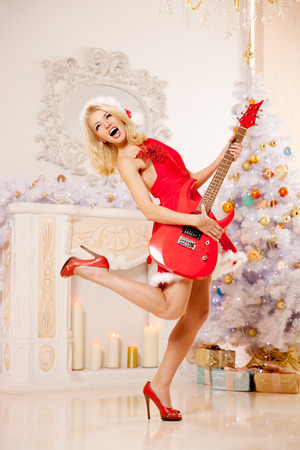 christmas music: Young beautiful smiling santa woman near the Christmas tree with bunny. Fashionable luxury  girl celebrating New Year with electric guitar. Stock Photo