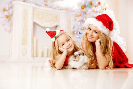 Mother and daughter dressed as Santa celebrate Christmas. Family at the Christmas tree. Woman and girl celebrate new year with bunny photo