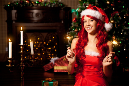 Young beautiful smiling santa woman near the Christmas tree. Fashionable luxury  girl celebrating New Year.  photo