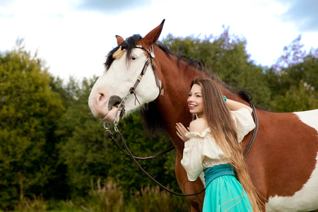 girl on horse: Beautiful young woman with a horse in the field. Girl on a farm with animal. Luxury woman outdoors  Stock Photo