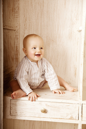 Beauty little baby sitting in the closet. Smiling child and interior of a bedroom. Cute kid photo