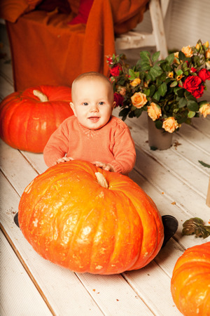 Beautiful young woman with a child on the front porch with pumpkins autumn. Smiling mother and son. photo