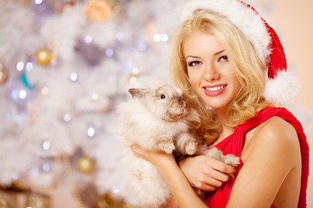 Young beautiful smiling santa woman near the Christmas tree with bunny. Fashionable luxury  girl celebrating New Year. photo