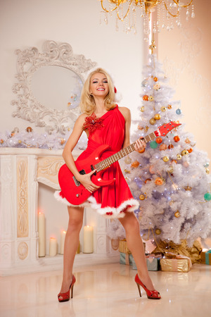 sexy guitar: Young beautiful smiling santa woman near the Christmas tree with bunny. Fashionable luxury  girl celebrating New Year with electric guitar. Stock Photo