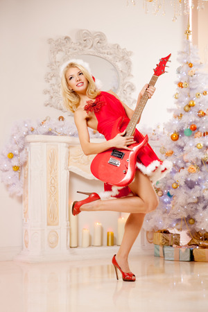 Young beautiful smiling santa woman near the Christmas tree with bunny. Fashionable luxury  girl celebrating New Year with electric guitar  photo