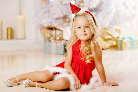 Beauty little Santa girl near the Christmas tree.  Happy girl celebrates  christmas. photo