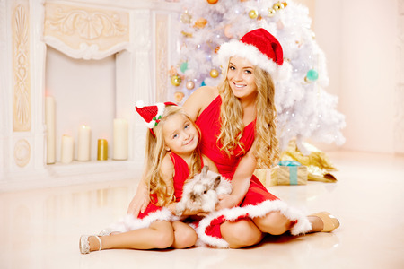 Mom and daughter dressed as Santa celebrate Christmas. Family at the Christmas tree. Woman and girl celebrate new year with bunny  photo