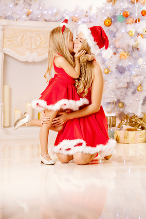 Mother and daughter dressed as Santa celebrate Christmas. Family at the Christmas tree. Woman and girl celebrate new year photo
