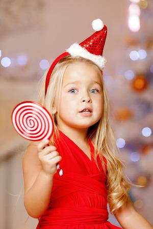 Beauty little Santa girl near the Christmas tree.  Happy girl celebrates christmas.  photo