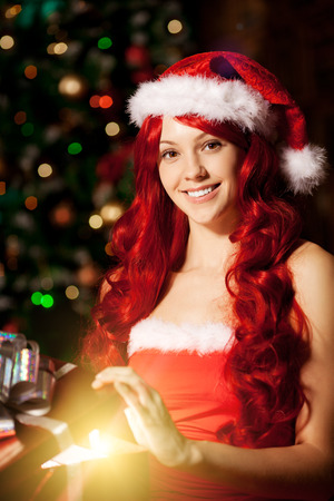 Young beautiful smiling santa woman near the Christmas tree with bunny. Fashionable luxury  girl celebrating New Year holding gift in hands photo
