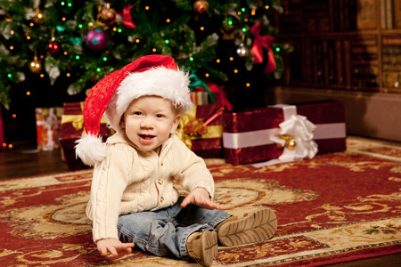 Nice baby near the Christmas tree. Little boy celebrating Christmas. Cute smiling child with New Year gifts. Christmas Toddler  photo