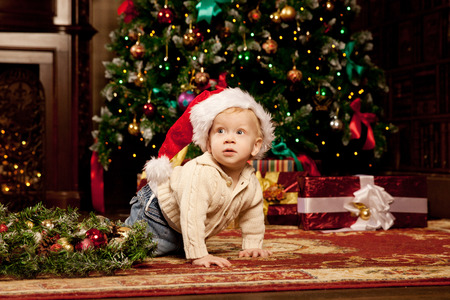 baby near christmas tree: Nice baby near the Christmas tree. Little boy celebrating Christmas. Cute smiling child with New Year gifts. Christmas Toddler