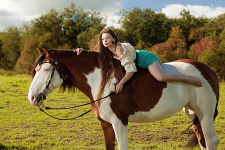 femme et cheval: Belle jeune femme avec un cheval dans le domaine. Fille sur une ferme avec des animaux. femme de luxe en plein air