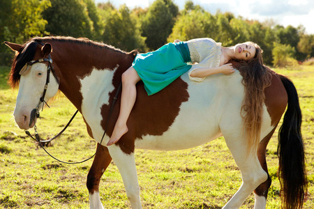 equitation: Beautiful young woman with a horse in the field. Girl on a farm with animal. Luxury woman outdoors Stock Photo