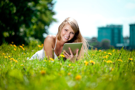 Portrait of young beautiful smiling woman with tablet pc, outdoors. Beautiful young girl lying on the grass in the field. Smiling trendy stylish woman on nature photo
