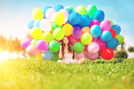 globos de cumpleaños: Feliz cumpleaños de la mujer contra el cielo con globos de aire colores del arco iris en sus manos. energía soleado y positiva de la naturaleza. Muchacha hermosa joven en la hierba en el parque. Foto de archivo