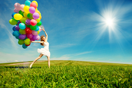 Happy birthday woman against the sky with rainbow-colored air balloons in hands. sunny and positive energy of nature. Young beautiful girl on the grass in the park. Banco de Imagens - 30697087
