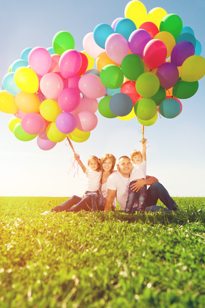 Happy family holding colorful balloons outdoor. Mom, ded and two daughters playing on  a green meadow.   photo