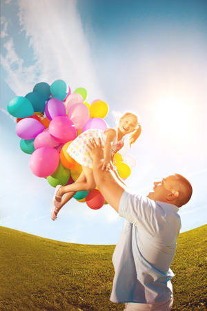 Father throws daughter. Familly playing together in park with balloons. Father tosses a baby against the sky photo