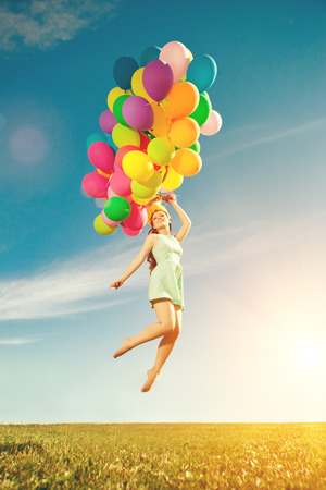 Luxury fashion stylish woman with balloons in hand on the field against the sky and 