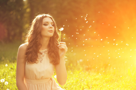 Beautiful young woman blowing  dandelion. Trendy young girl at sunset with flower  photo