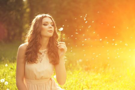 Mooie jonge vrouw blaast paardebloem. Trendy jonge meisje bij zonsondergang met bloem