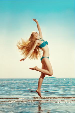 bikini model: Beautiful slim woman on the beach by the sea Stock Photo