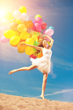 Beauty young stylish woman with multi-colored rainbow balloons in hands against the sky. Positive girl on nature. Smiling woman outdoors enjoying. photo