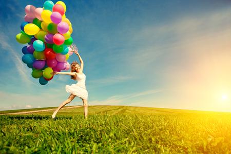 手で虹色の気球が付いている空に対してお誕生日おめでとう女。自然の日当たりの良い、肯定的なエネルギー。公園の芝生の上の美しい少女。