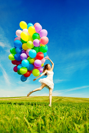 colorful sky: Happy birthday woman against the sky with rainbow-colored air balloons in her hands. sunny and positive energy of nature. Young beautiful girl on the grass in the park.