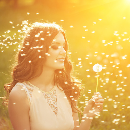 Beautiful young woman blowing a dandelion. Trendy young girl at sunset with flower photo